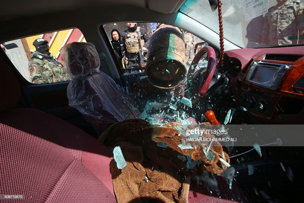 Iraqi security forces break into a car in the Nahr al-Ezz area, 150km North of Basra, on February 12, 2016 during a security operation. Operations by the security forces, including the intelligence services, are regular in the area in an attempt to contain and disarm feuding local gangs and tribes. / AFP / HAIDAR MOHAMMED ALI