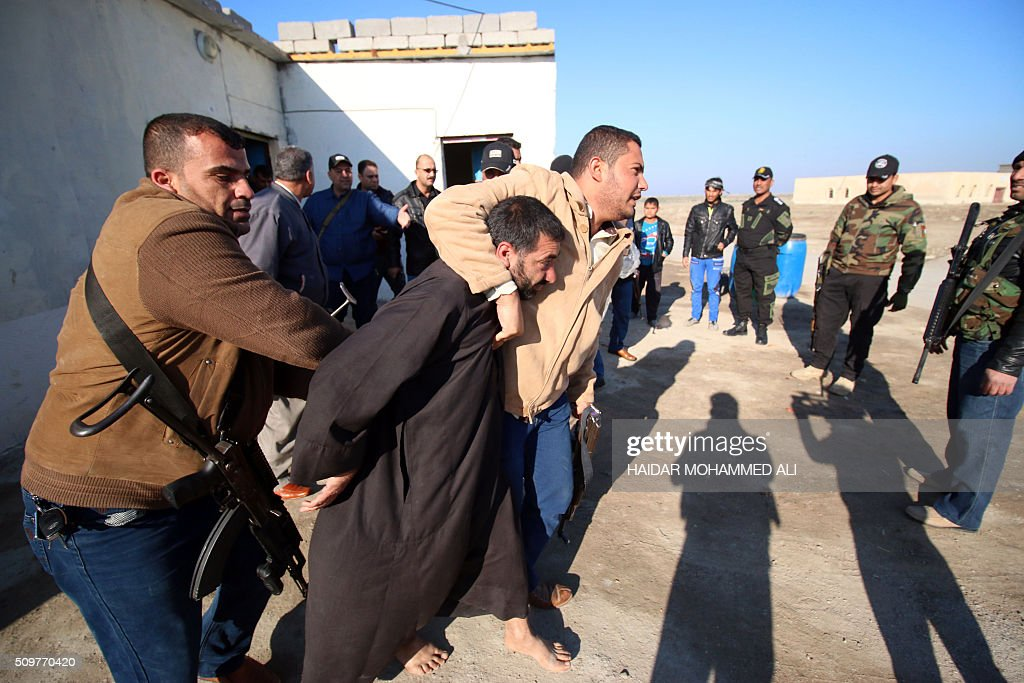 Iraqi security forces detain a suspect in the Nahr al-Ezz area, 150km North of Basra, on February 12, 2016 during a security operation. Operations by the security forces, including the intelligence services, are regular in the area in an attempt to contain and disarm feuding local gangs and tribes. / AFP / HAIDAR MOHAMMED ALI