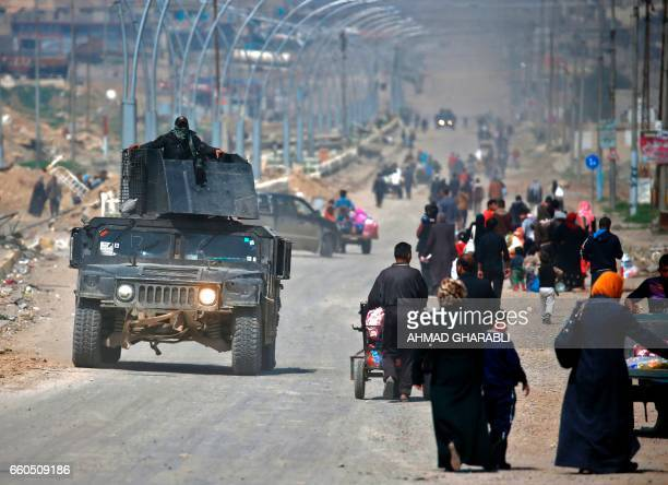 TOPSHOT Iraqi security forces drive past civilians fleeing their homes in Mosul's old city on March 30 due to the ongoing battles between government...