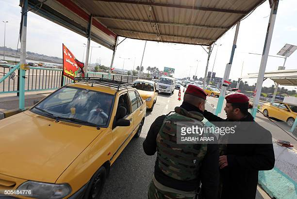 Iraqi security forces man a checkpoint on the main road from Baghdad's central Jaderiyah district to Dora on the southern outskirts of the Iraqi...