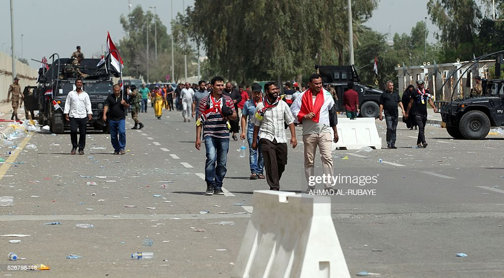 Iraqi security forces patrol the area as Iraqis walk outside the cabinet building in Baghdad's heavily fortified 'Green Zone' on May 1, 2016, the day after supporters of Shiite cleric Moqtada al-Sadr broke into the area after lawmakers again failed to approve new ministers. Thousands of wide-eyed Iraqis marvelled at the fountains, flowers and perfect lawns in the capital's Green Zone, a day after protesters breached the walls of the fortified area. The visitors were mostly protesters who broke in but also included Baghdadis taking the opportunity to see an area that was off-limits for so many years that it acquired almost mythical status in the psyche of ordinary citizens RUBAYE