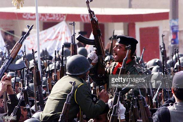 Iraqi security forces raise their guns during a parade March 5 2003 in Baghdad Iraq Thousands of security troops and 120 wouldbe suicide bombers...