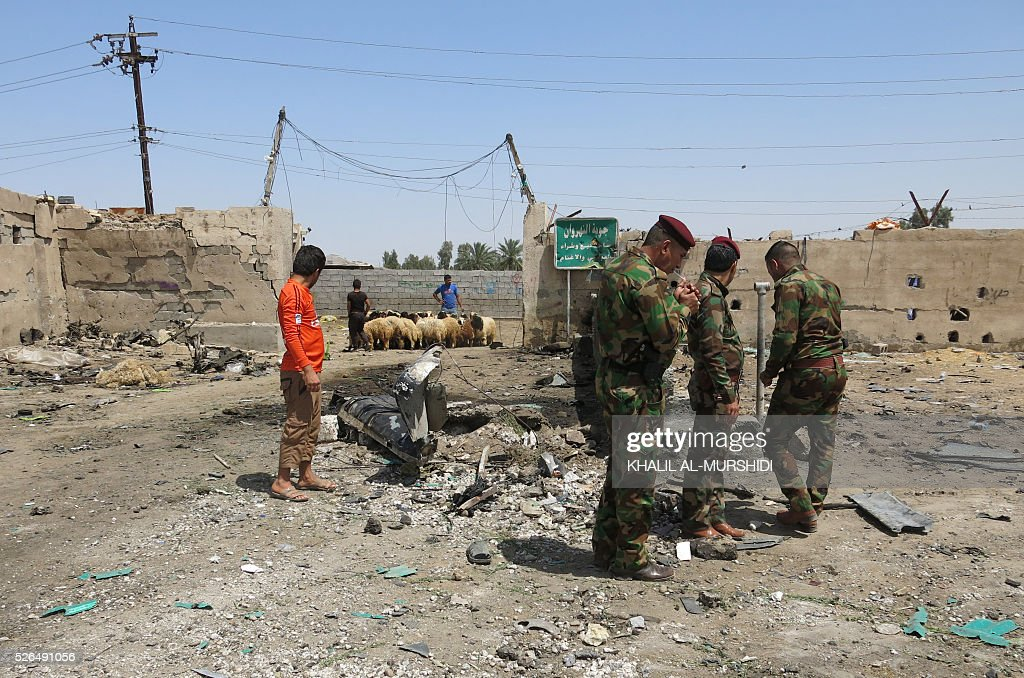 Iraqi security forces stand at the site of a car bomb attack that targeted Shiite pilgrims in Baghdad's Nahrawan area on April 30, 2016. The bomb, which killed at least 14 people, was left on a road in the Nahrawan area used by Shiite pilgrims who are walking to the shrine of Imam Musa Kadhim in northern Baghdad for annual commemorations. / AFP / KHALIL