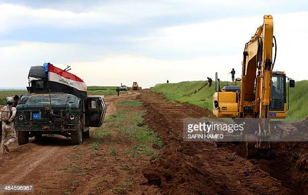 Iraqi security forces stand guard as workers are digging a trench on the northern Iraqi border with Syria to prevent people from crossing over into...