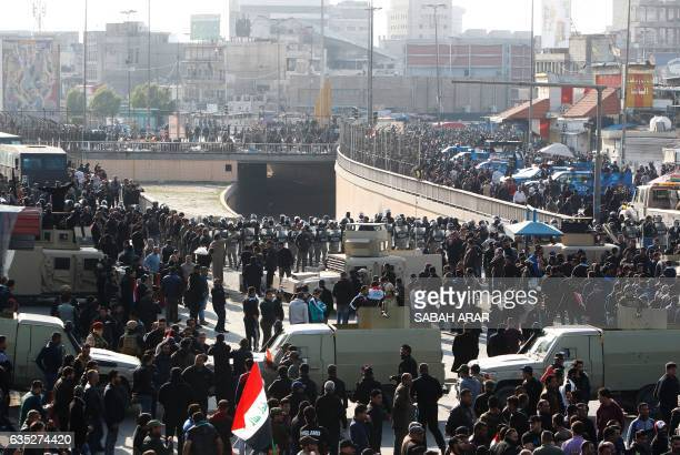 Iraqi security forces stand guard during a mock funeral procession mostly attended by supporters of prominent cleric Moqtada Sadr in Baghdad on...