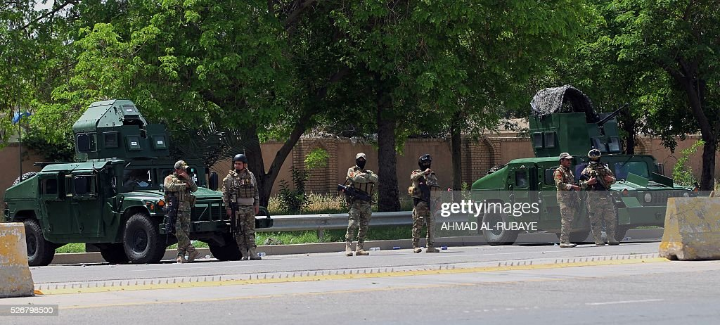Iraqi security forces stand guard in Baghdad's heavily fortified 'Green Zone' on May 1, 2016, the day after supporters of Shiite cleric Moqtada al-Sadr broke into the area after lawmakers again failed to approve new ministers. Thousands of wide-eyed Iraqis marvelled at the fountains, flowers and perfect lawns in the capital's Green Zone, a day after protesters breached the walls of the fortified area. The visitors were mostly protesters who broke in on Saturday but also included Baghdadis taking the opportunity to see an area that was off-limits for so many years that it acquired almost mythical status in the psyche of ordinary citizens. RUBAYE