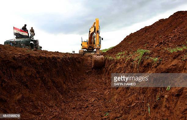 Iraqi security forces watch as a worker uses a digger to build a trench on the northern Iraqi border with Syria to prevent people from crossing over...