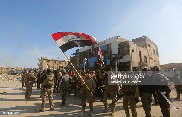 Iraqi security forces wave their national flag on December 28 2015 in front of the Anbar police headquarters after they recaptured the city of Ramadi...
