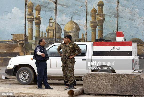 Iraqi security stand in front of painted cement blast walls outside the destroyed Baghdad Governorate building targeted by a suicide bomber two days...