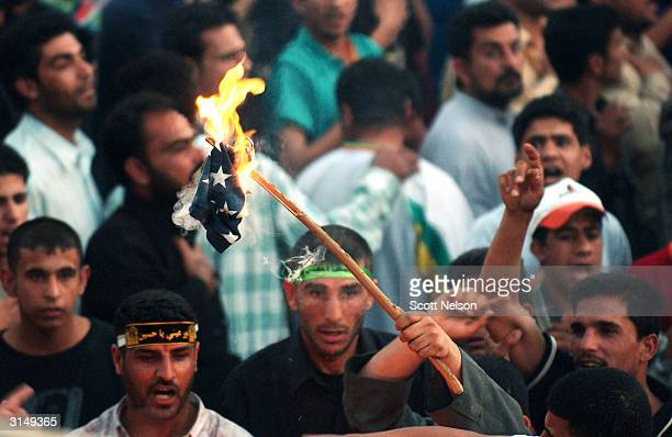 Iraqi Shia burn a US flag as they protest the Coalition Provisional Authority's ordered closure of the AlHawza newspaper office March 28 2004 in...