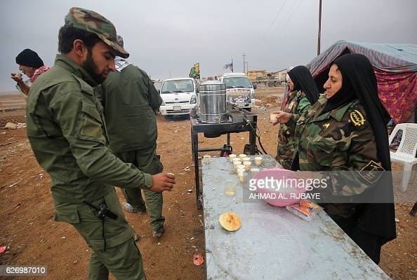 Iraqi Shia women distribute tea to Iraqi fighters in the village of Arabat south of Mosul as temperatures continue to drop on December 1 2016 Tens of...