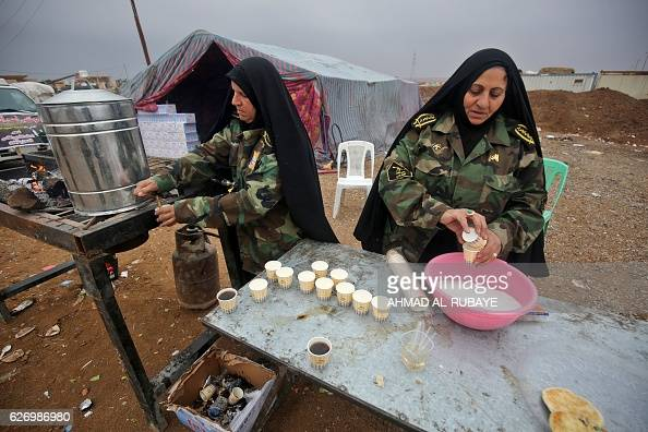 Iraqi Shia women prepare tea for Iraqi fighters in the village of Arabat south of Mosul as temperatures continue to drop on December 1 2016 Tens of...
