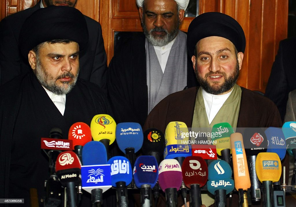 Iraqi Shiite cleric Moqtada al-Sadr (L) and Iraqi Shiite Muslim leader Ammar al-Hakim speak during a meeting to discuss economic and security issues held at Hakim's house in the southern Shiite city of Najaf on January 23, 2015. Al-Sadr expressed his hopes for a unity government and encouraged the efforts of Iraqi Prime Minister Haider al-Abadi in avoiding previously made mistakes. AFP PHOTO/ HAIDAR HAMDANI