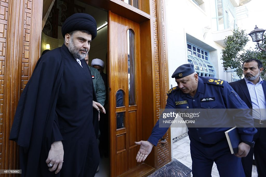 Iraqi Shiite cleric Moqtada al-Sadr (L) arrives for a press conference with Iraqi Defence Minister Khaled al-Obeidi following a meeting on January 19, 2015 in the holy city of Najaf.
