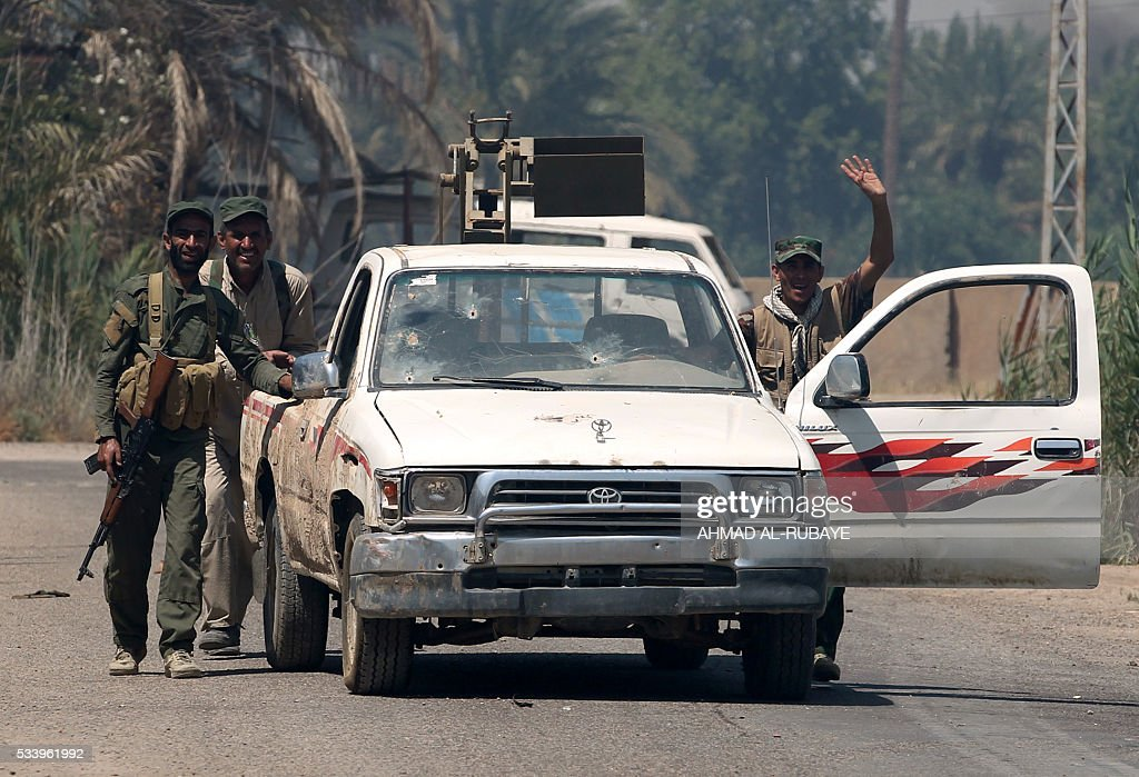 Iraqi Shiite fighters from a Popular Mobilisation push a vehicle reportedly seized from jihadists of Islamic State (IS) group near the city of Fallujah on May 24, 2016 during an assault by Iraqi forces to retake the city from IS. Iraqi forces, consisting of special forces, soldiers, police, militia forces and pro-government tribesmen, launched a major assault to retake Fallujah, the scene of deadly battles during the US occupation and one of the toughest targets yet in Baghdad's war on the Islamic State group. RUBAYE