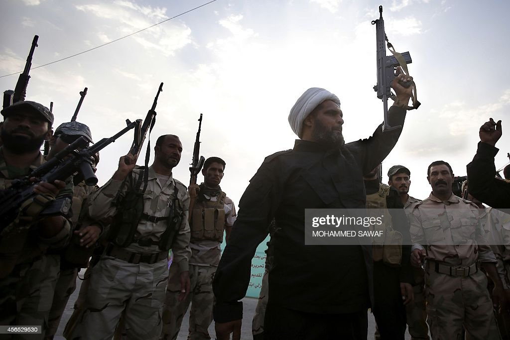 Iraqi Shiite fighters from Tal Afar loyal to Grand Ayatollah Ali alSistani raise their weapons as they take part in a parade in the Shiite shrine...
