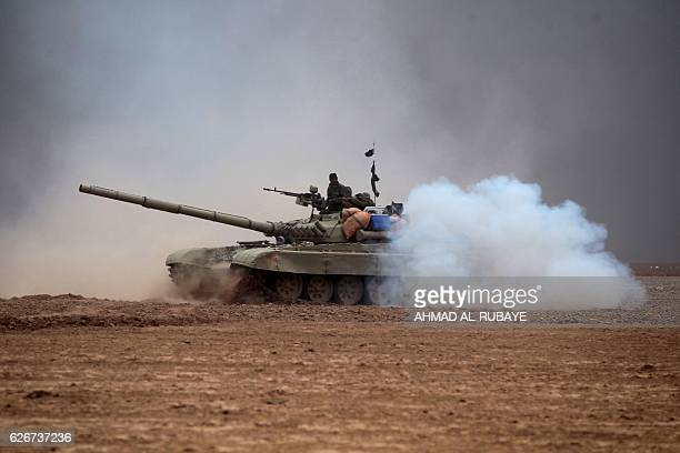 Iraqi Shiite fighters from the Hashed alShaabi paramilitaries manoeuver a T72 tank as they advance near the town of Tal Abtah south of Tal Afar on...