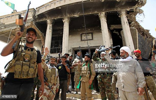 Iraqi Shiite fighters from the Popular Mobilisation force raise their weapons in front of a heavily damaged building as they continue to battle...