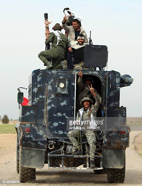 Iraqi Shiite fighters from the Popular Mobilisation units and security forces drive down a road in the desert of Samarra on March 3 during an...