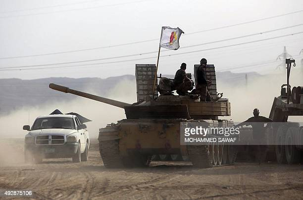 Iraqi Shiite fighters from the Popular Mobilisation units and Iraqi government forces drive a tank in the town of Baiji north of Tikrit during...