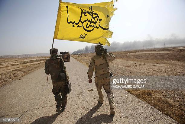 Iraqi Shiite fighters from the Popular Mobilisation units fighting alongside Iraqi forces walk in the town of Baiji north of Tikrit during fighting...