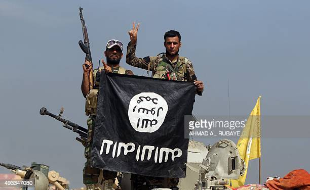 Iraqi Shiite fighters from the Popular Mobilisation units fighting alongside Iraqi government forces display upside down the flag of the Islamic...
