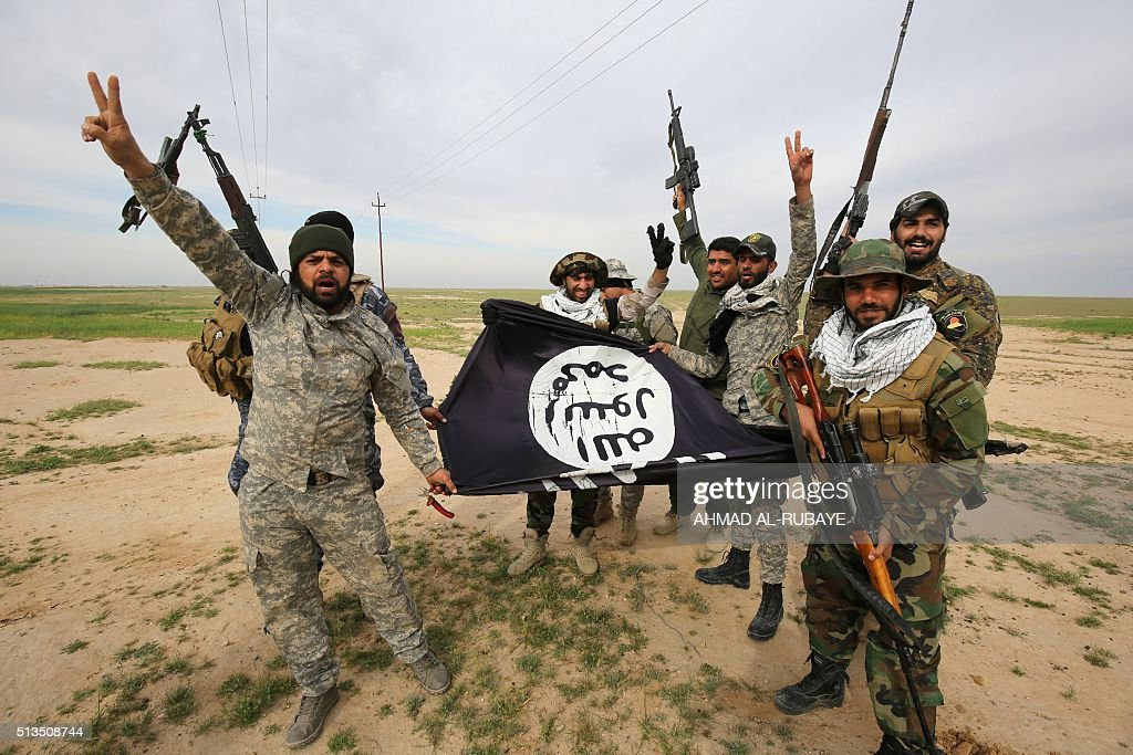 Iraqi Shiite fighters from the Popular Mobilisation units pose with a Islamic State (IS) group flag on March 3, 2016, during an operation in the desert of Samarra aimed at retaking areas from IS jihadists. Counter-terrorism forces, soldiers, police and allied paramilitaries are taking part in an operation launched on March 1, which is backed by artillery and both Iraqi and US-led coalition aircraft, aimed at retaking areas north of Baghdad, according to the Joint Operations Command. An Iraqi army colonel said that more than 7,000 security personnel would take part in the operation, which the operations command said aims to retake areas west of the city of Samarra. / AFP / AHMAD