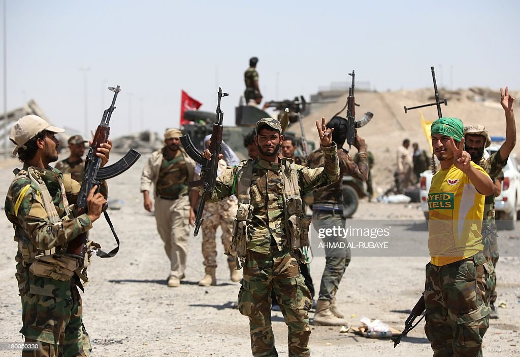 Iraqi Shiite fighters from the Popular Mobilisation units supporting the Iraqi government forces flash the sign for victory as they gather on the...