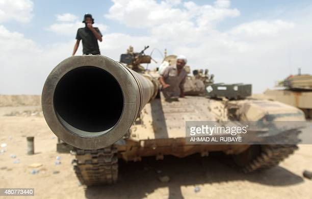 Iraqi Shiite fighters from the Popular Mobilisation units supporting the Iraqi government forces guard a position on a tank on July 15 2015 on the...