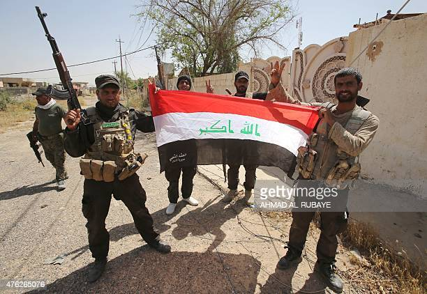 Iraqi Shiite fighters from the Popular Mobilization units hold an Iraqi flag in the city of Baiji north of Tikrit in the Salahaddin province on June...