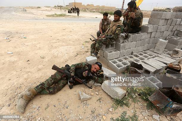 Iraqi Shiite fighters of the governmentcontrolled Popular Mobilisation units wait as they take a position in a suburb west of the city of Tikrit on...