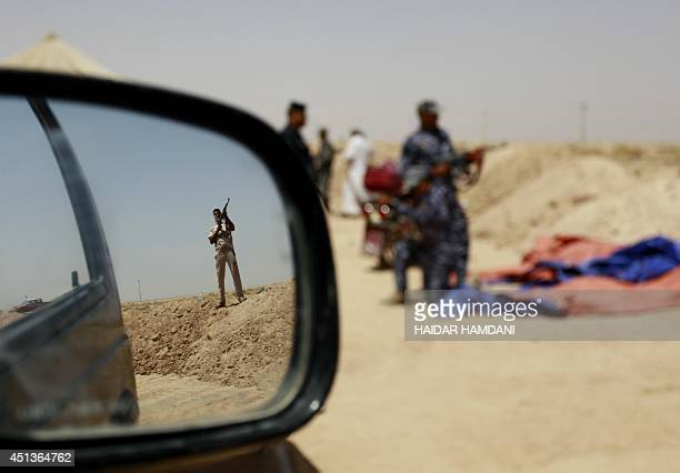 Iraqi Shiite fighters secure an area West of the central holy city of Najaf on a road leading to the restive Anbar province on June 28 2014 Iraq's...