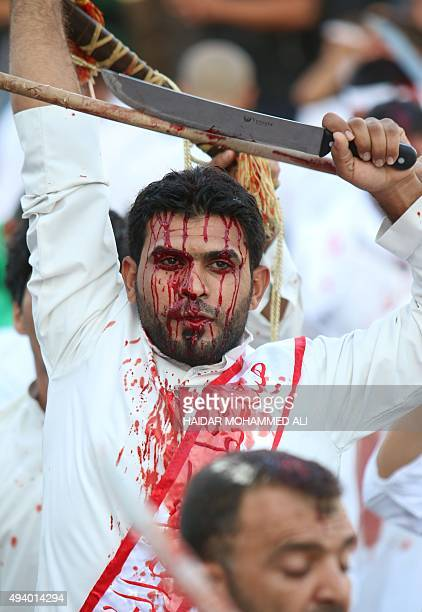Iraqi Shiite men cut their scalps with machetes as they take part in the Ashura religious ritual on October 24 2015 in the mainly Shiite southern...