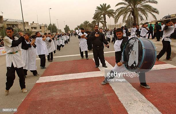 Iraqi Shiite men flagellate themselves on February 12 2005 as they walk on a Danish flag painted on the ground in a protest over the publication of...