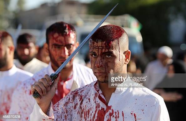 Iraqi Shiite men take part in a selfflagellation procession during the Ashura commemorations that mark the killing of Imam Hussein one of Shiite...