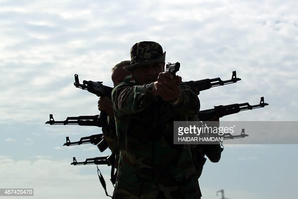 Iraqi Shiite men who have volunteered to join government forces and militias in the fight against jihadists from the Islamic State group take part in...