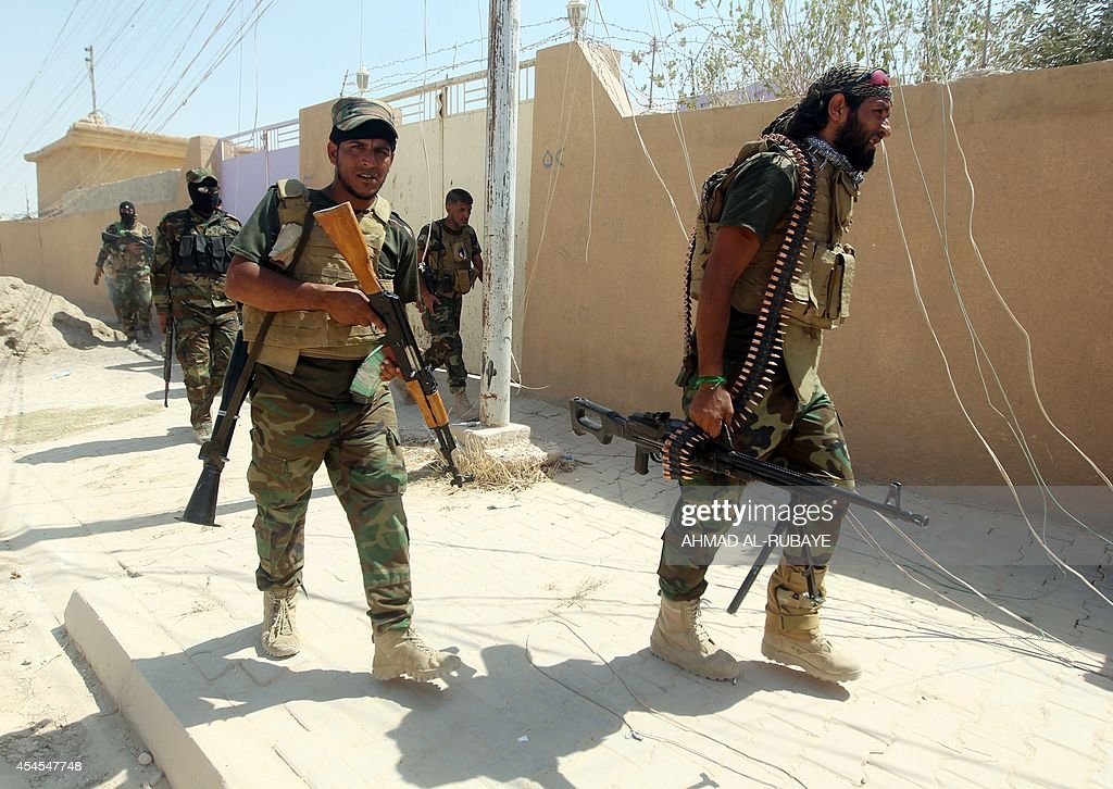 Iraqi Shiite militia fighters walk on the side of the road after they pushed back Islamic State militants on September 3 on the road between Amerli...