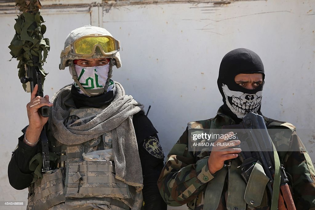 Iraqi Shiite militia fighters wearing masks look on near Amerli on September 3 after pushing back Islamic State militants Amerli was besieged when...