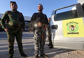 Iraqi Shiite militiamen walk after a conference on fighting the Islamic State group attended by Iraq's tribal leaders the army and members of the...