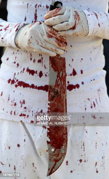 Iraqi Shiite Muslim holds a sword covered with blood during a selfflagellation ritual marking Ashura that commemorates the 7th century killing of...