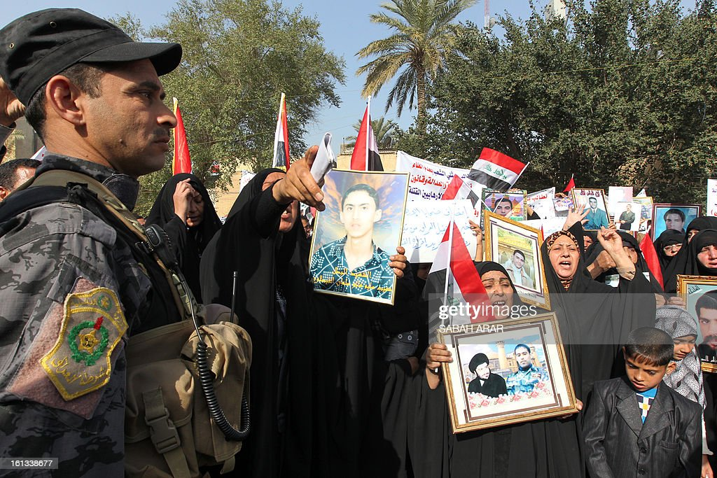 Iraqi Shiite Muslims hold photos of relatives during a rally in the capital Baghdad on February 10, 2013, protesting against a call to abolish the de-Baathification law which bans senior members of the regime of former Iraqi president Saddam Hussein from government employment, the modifications to the anti-terrorism laws and an amnesty for Sunni prisoners convicted on terrorism charges, brought into effect following the fall of Saddam Hussein in April 2013. The rally follows weeks of protests by the Sunnis hoping that through their protests and sit-ins that have swept across Sunni provinces and Baghdad's Sunni neighbourhoods they can abolish the political structure forged by the US occupation authority, allowing them to negotiate a more equitable governing system.