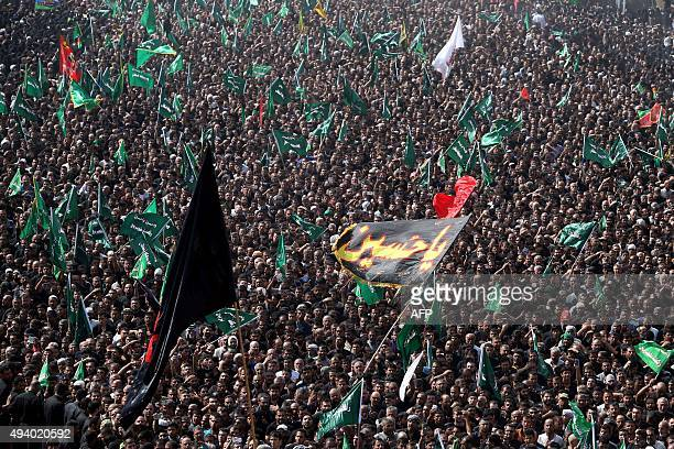 Iraqi Shiite Muslims take part in a procession between the shrines of Imam Hussein and Imam Abbas to mark Ashura on the tenth day of the mourning...