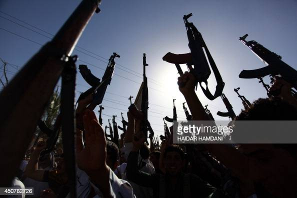 Iraqi Shiite tribesmen brandish their weapons as they gather to show their willingness to join Iraqi security forces in the fight against Jihadist...
