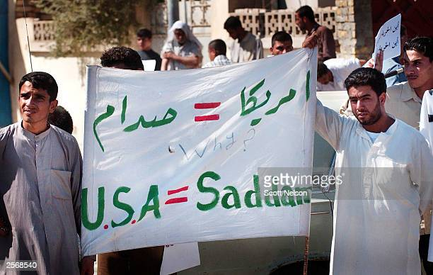 Iraqi Shiites carry an antiUS banner during an protest against the detention of local Shia Imam Mo'ayed alKhezragi by US military by US military...