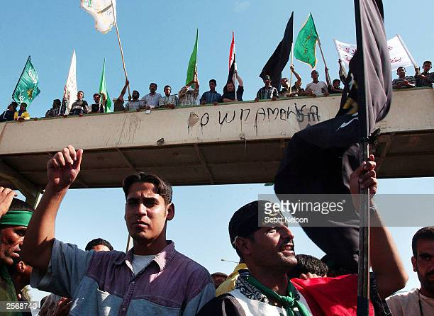 Iraqi Shiites carrying antiUS banners chant slogans during during a protest against the detention of local Shia Imam Mo'ayed alKhezragi by US...
