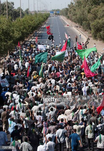 Iraqi Shiites march down the main road to the airport during a protest against the detention of local Shia Imam Mo'ayed alKhezragi by US military...