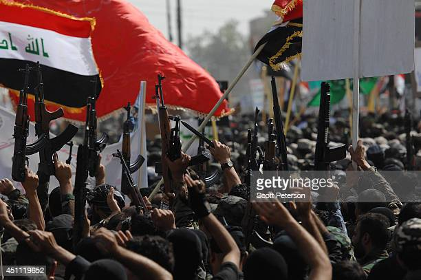 Iraqi Shiites of the Mahdi Army militia loyal to cleric Moqtada alSadr raise their weapons and flags as they vow to fight ISIS in a show of strength...