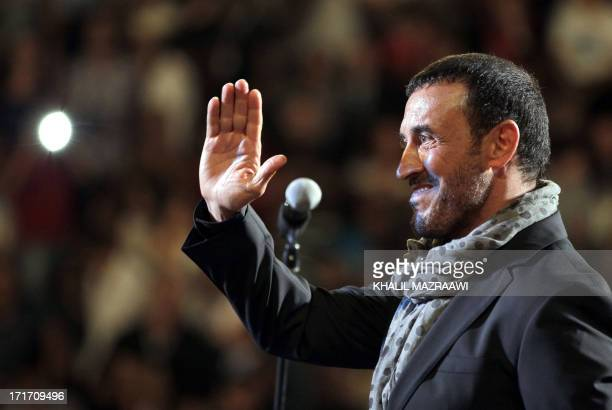 Iraqi singer Kazem alSaher waves to fans as he performs on stage during a concert at the Jarash Festival of Culture and Arts on June 27 2013 at the...