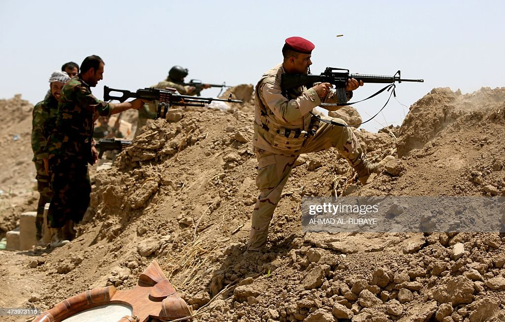 Iraqi soldiers and Shiite fighters from the popular committees hold a post as they fire towards Islamic State group positions in the Garma district...