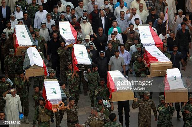Iraqi soldiers carry coffins containing the remains of ten of their comrades who were killed in the Speicher massacre after they were handed over to...